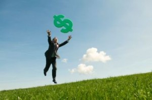 Man Chasing After A Dollar Sign In an Open Field